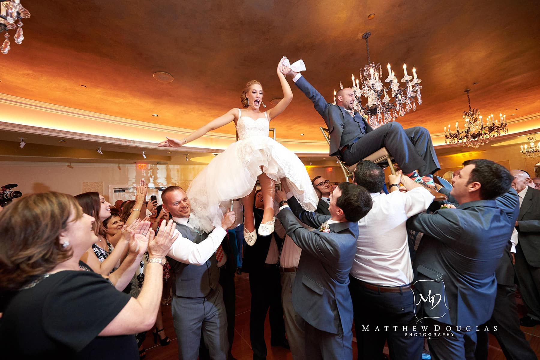 bride and groom lifted during the hora at The Farmhouse at The Grand Colonial